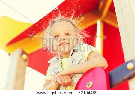 summer, childhood, leisure and people concept - happy little girl on children playground