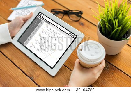 business, education, technology, people and programming concept - close up of woman with coding on tablet pc computer screen and coffee cup on wooden table