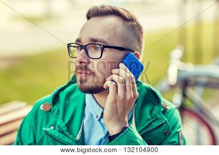people, style, technology and lifestyle - young hipster man calling on smartphone and sitting on bench in city