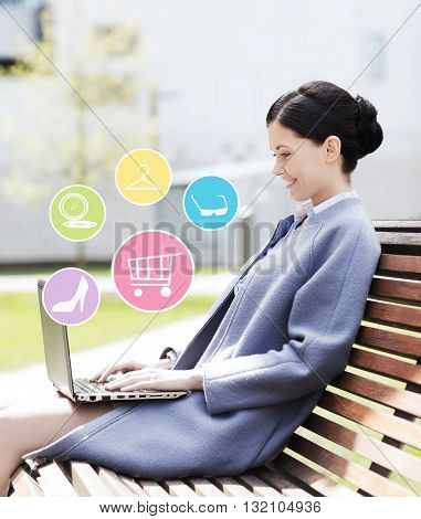 business, technology, online shopping and people concept - young smiling woman with laptop computer and internet icons sitting on bench in city