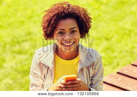 technology, communication and people concept - smiling african american young woman or teenage girl messaging on smartphone at summer park