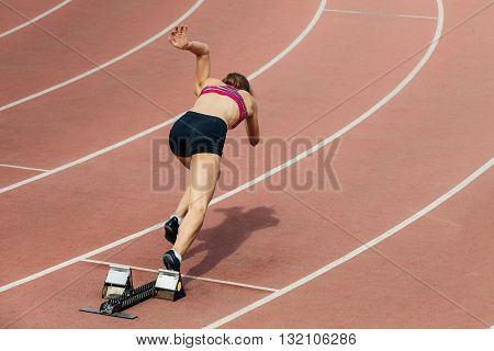 girl sprinter at start of 400 metres at stadium
