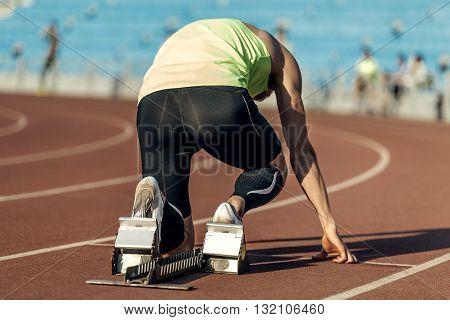 male athlete in starting blocks. running at sprint at stadium