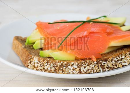 Close up of a healthy sandwich with avocado, smoked salmon and rye bread