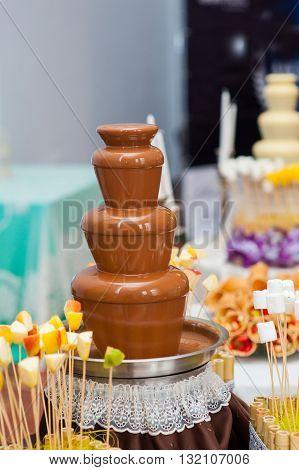 Chocolate fondue fountain of dark chocolate being dipped.