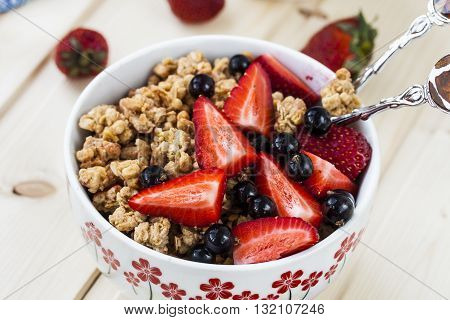 Healthy breakfast with granola milk honey and fresh berries