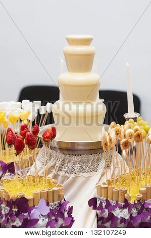 Chocolate fondue fountain of white chocolate being dipped.