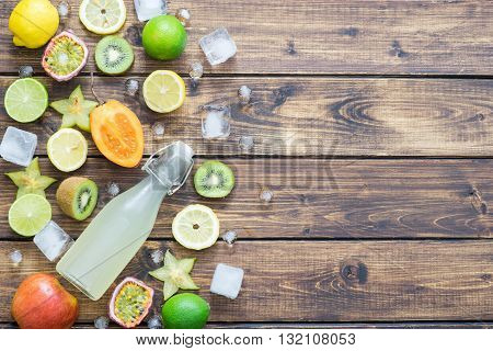 Tropical fruits with ice and a bottle of refreshing soda making a left border on wooden background with a space for yout text