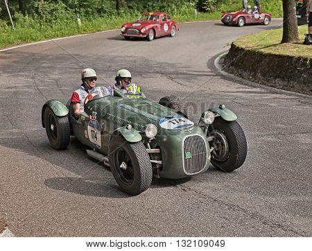 PASSO DELLA FUTA (FI) ITALY - MAY 21: driver and co-driver on a vintage competition car HW Alta 2000 Sport B1 (1949) in classic car race Mille Miglia on May 21, 2016 in Passo della Futa (FI) Italy