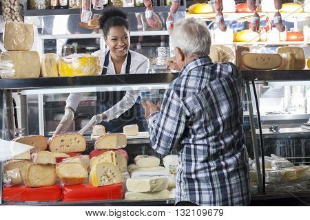 Saleswoman Selling Cheese To Senior Man At Shop