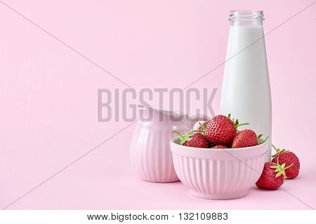 A food background with a bowl full of fresh strawberries, milk bottle and milk jar. Pink colors.