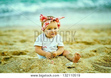 beautiful little girl playing with sand on the sea shore