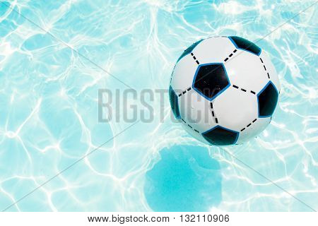 Beach ball in the blue swimming pool