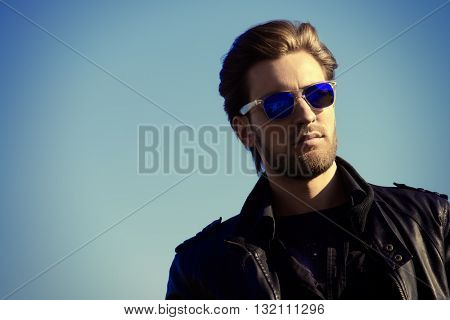 Confident handsome man in sunglasses and leather jacket over blue sky. Men's beauty, fashion. Outdoor portrait.