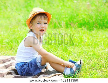 Happy Child Boy In Hat Sitting On Grass In Summer Day