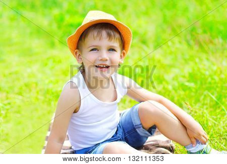 Happy Little Boy Child In Hat Sitting On The Grass In Summer Day