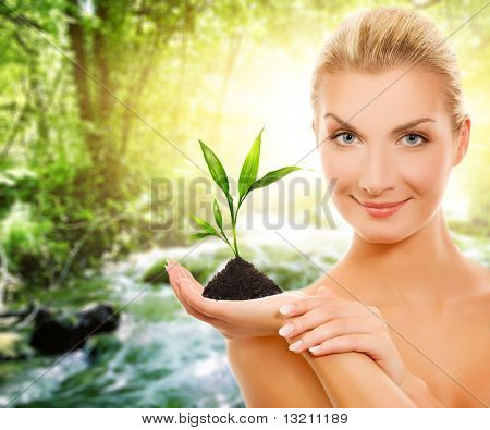 Beautiful woman with young plant in forest