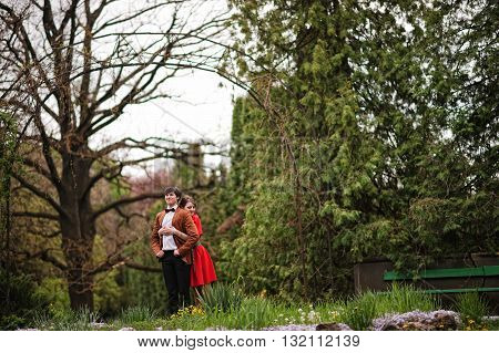 Couple Hugging In Love At Park Garden Background Big Arch. Stylish Man At Velvet Jacket And Girl In