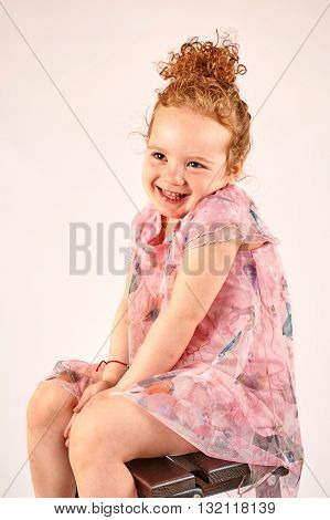 Fashion little girl in rose dress in catwalk model pose stock photo
