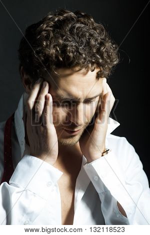 Handsome sexy man with curly hair and unshaven face in white shirt and red untied bow holding hands near head in headache on black background