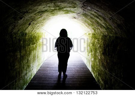 Silhouette of woman standing at end of tunnel - light at end of tunnel