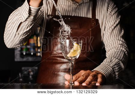 splash in a glass with lemon on bar barman on background