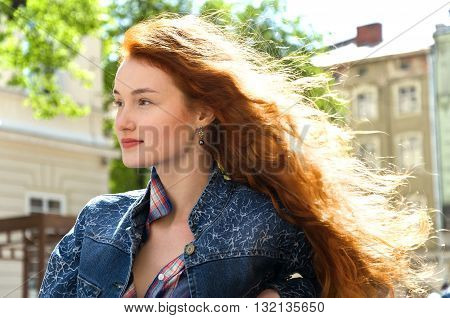 girl with red curly hair. wind blew away hair