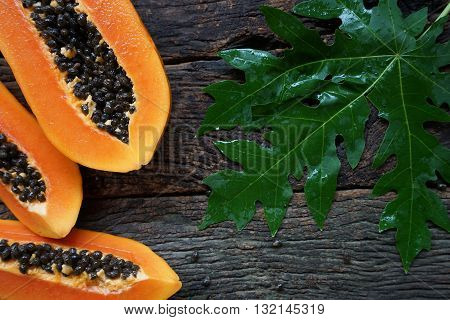 Top View Ripe Papaya With Green Leaf On Old Wooden Background.