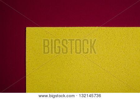 Eva foam ethylene vinyl acetate sponge plush lemon yellow surface on red smooth background