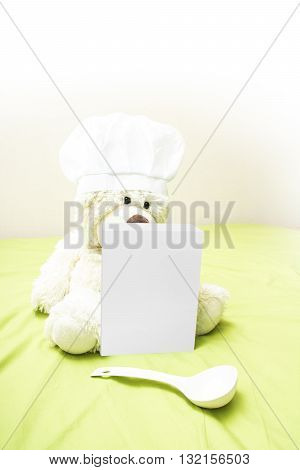Teddy bear in a chef's hat touting a box of baby food. Teddy bear sitting next to a box of children's gruel and spoon. The concept of advertising for baby nutrition. Blank packaging paper box.