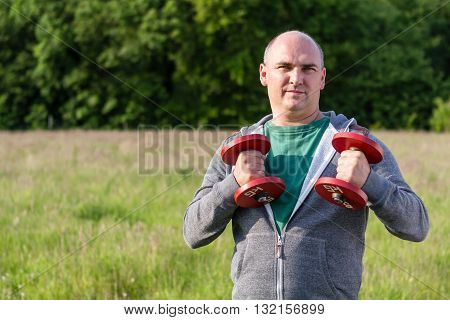 Man holds up 5 kilo dumbbells. He holds one up.