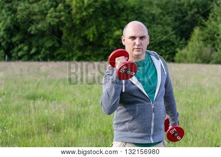 Man working outdoors with 5kg dumbbells. He holds one up.