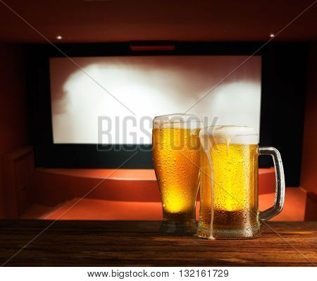 excellent beer on a wooden table against the background of a movie screen