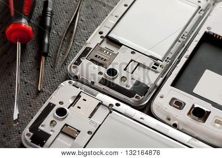 Disassembled cell phone with tools selective focus