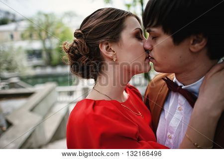 Close Up Portrait Of Kissing Couple. Stylish Man At Velvet Jacket And Bow Tie And Girl In Red Dress.