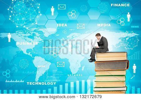 Businessman with laptop sitting on stack of books on blue background with world map