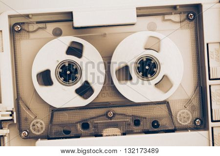 rewinding of vintage audio tape compact cassette, sepia tone with artistic film noise
