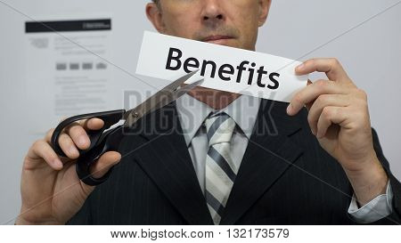 Male office worker or businessman in a suit and tie cuts a piece of paper with the word benefits on it as a benefits reduction business concept.