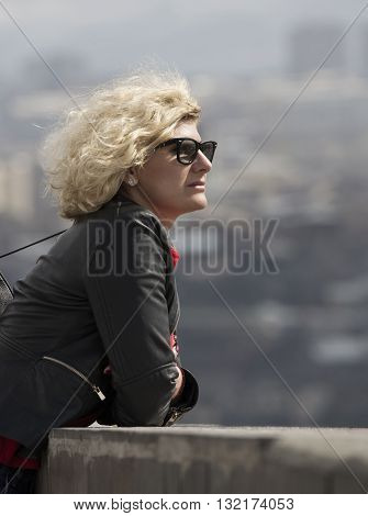 Beautiful blondie woman with curly hair is looking into the distance
