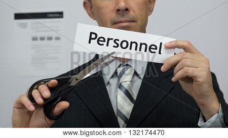 Male office worker or businessman in a suit and tie cuts a piece of paper with the word personnel on it as a personnel reduction business concept.