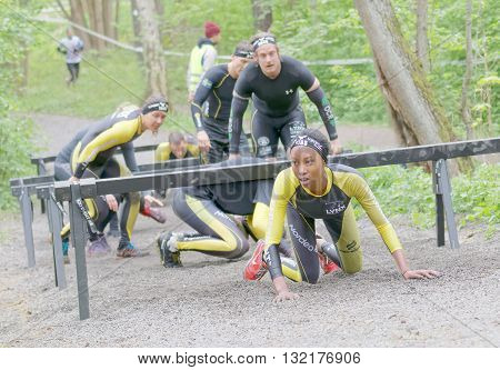 STOCKHOLM SWEDEN - MAY 14 2016: African woman and competitors crawling under bars in the obstacle race Tough Viking Event in Sweden May 14 2016