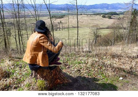 Lonely girl in forest sitting on tree