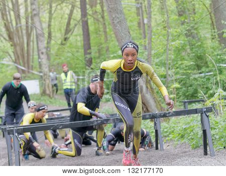 STOCKHOLM SWEDEN - MAY 14 2016: African woman and competitors crawling under bars in the obstacle race Tough Viking Event in Sweden April 14 2016