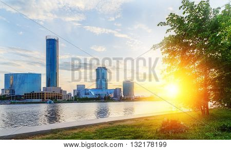 sun and the beautiful sunset over city center and city pond of Yekaterinburg in summer
