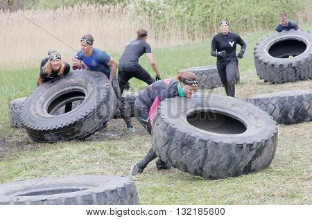 STOCKHOLM SWEDEN - MAY 14 2016: Group of men and woman struggling to tip a large tractor tire obstacle in the obstacle race Tough Viking Event in Sweden April 14 2016