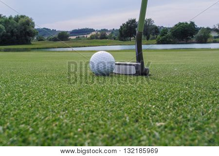 a golf ball and a putter in a beautiful green