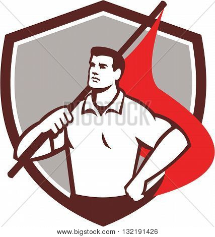 Illustration of a union worker holding red flag on shoulders with one hand on hips looking to the side set inside shield crest done in retro style.