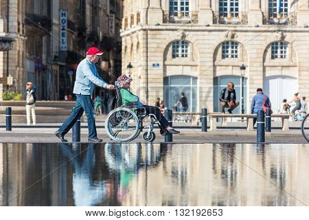 People Visiting A Mirror Fountain In Bordeaux, France