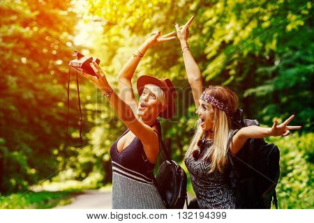 Two woman taking self portrait along the road through woods