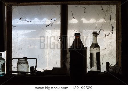 Bottles are on a window in a barn.